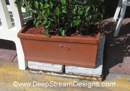 Ceramic restaurant planter with peeling paint..