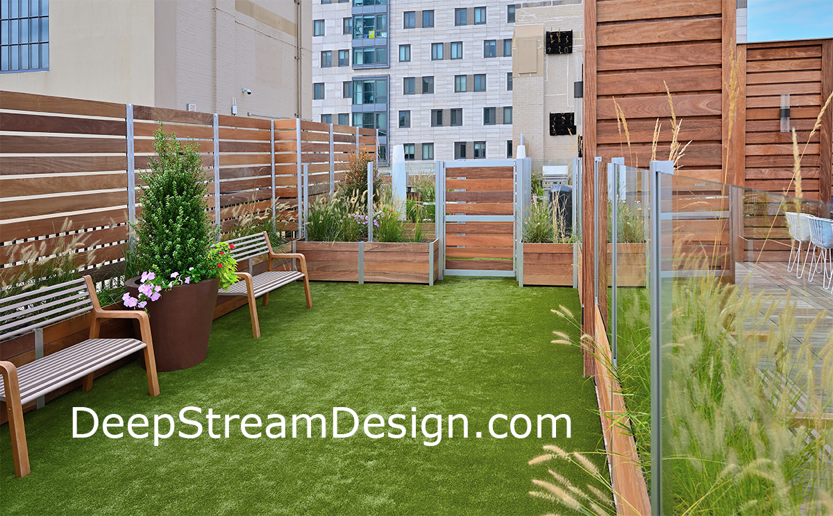 Large multi section prefabricated modular commercial wood planters with their aluminum frame anchor glass and wood screen wall and gates, without roof penetrations, creating the tenants' favorite amenity, a dog park on the roof deck. Click for Info