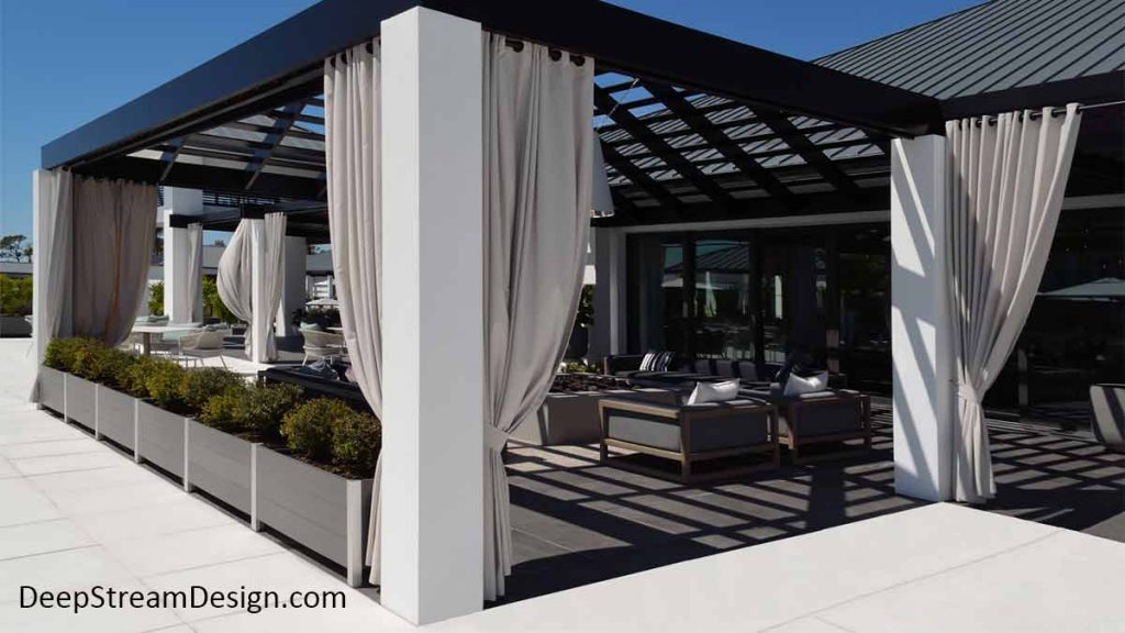 Modern Planters in slate grey no-maintenance recycled plastic lumber and anodized aluminum control access to a modern clubhouse outdoor lounge with long white curtains pulled back around a ceiling shade grid open to the bright blue sky.