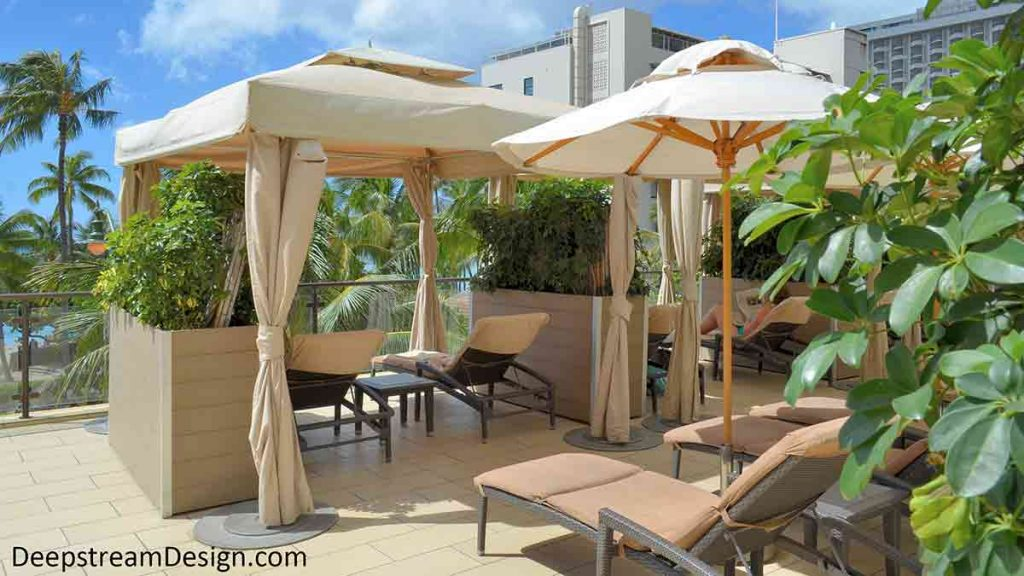 42 inch high tall commercial wood planters, in maintenance free recycled plastic lumber, feature casters for mobility allowing privacy between massage tables on the pool terrace of a Waikiki waterfront hotel.