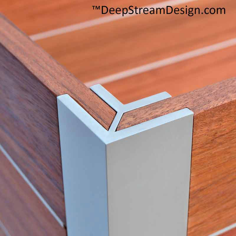 Studio photo showing a Mariner Structural Architectural Aluminum Frame System L corner extrusion holding two wood panels of a planter at 90 degrees to for the corner of a wood planter.