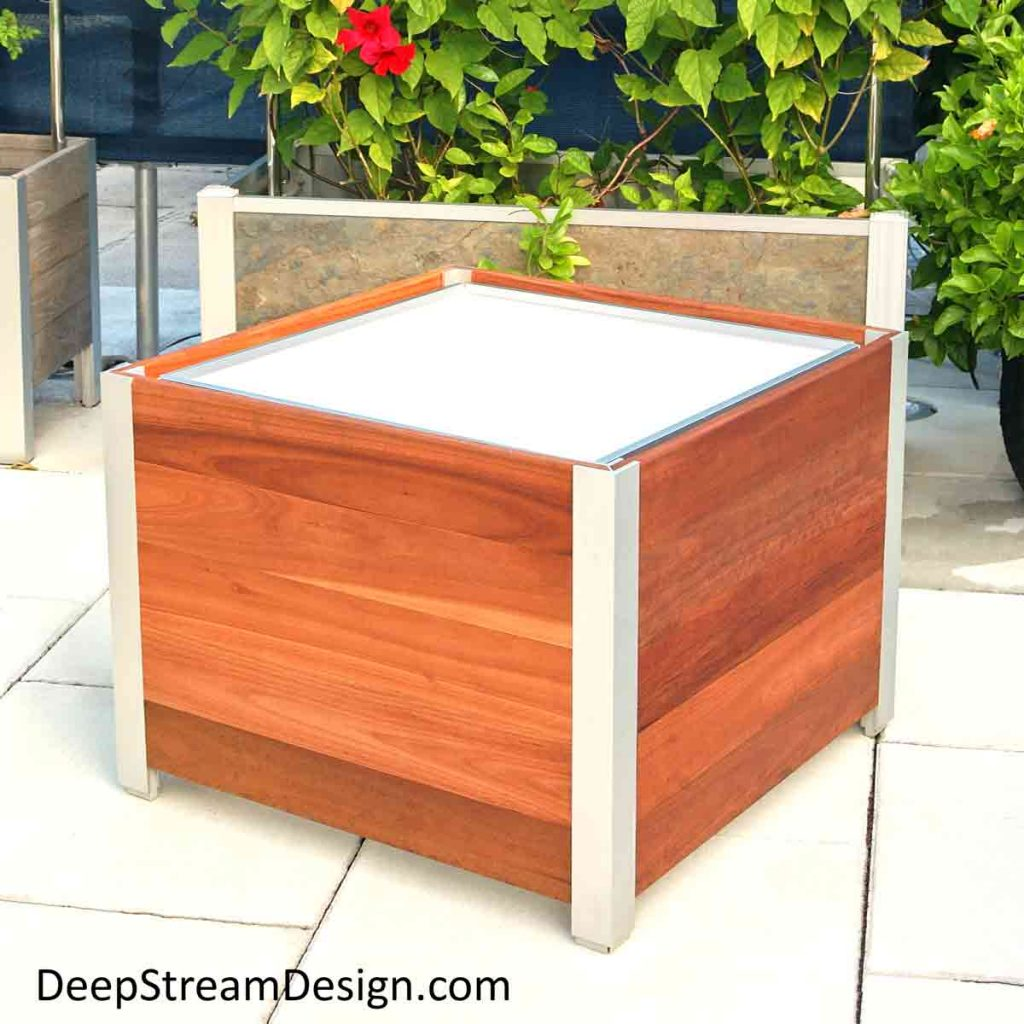 A Modern Planter hand made from cumaru wood to custom specification by American craftsmen, shown unplanted with a waterproof planter liner inserted inside that his held by a hidden structural aluminum frame. Behind this front Modern Planter is a larger Modern Planter hand crafted from natural slate that holds a trellis covered in a green vine with bright red flowers that acts as a privacy screen blocking the view of air conditioning equipment behind it on a tropical roof deck.